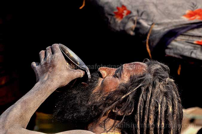 Culture- Naga Sadhu\u2019s (India) - A Naga Sadhu having water at Ghats in Varanasi. by Anil Sharma Fotography