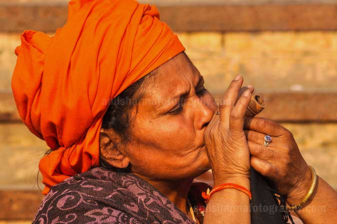 Culture- Naga Sadhu\u2019s (India) - A women Naga Sadhu enjoying clay pipe smoking at Varanasi ghat. by Anil