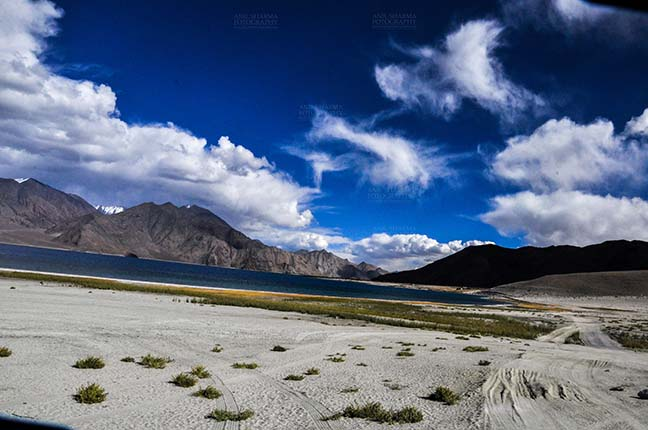 Clouds- Sky with Clouds (Pangong Tso) - Clouds over Pangong Tso, Leh, Jammu and Kashmir, India- October 1, 2014: Dark blue sky with Bright white clouds over the Pangong Tso and surrounding hills at Leh, Jammu and Kashmir, India. by Anil Sharma Fotography