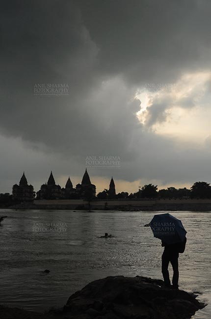 Monuments- Palaces and Temples of Orchha - DSC_0337 Orchha, Madhya Pradesh, India- August 20, 2012: Chhatris on the bank of river Betwa, a tourist holding umbrella enjoying cloudy- rainy weather at Orchha, Madhya Pradesh, India. by Anil