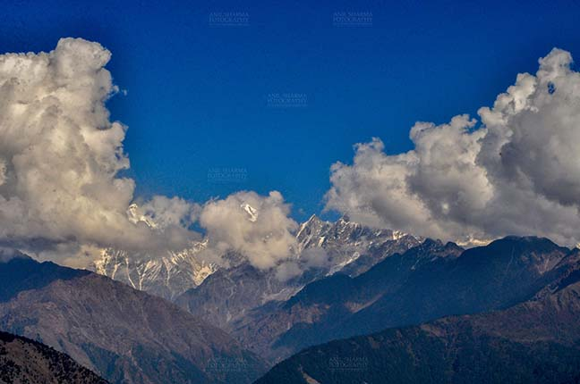 Clouds- Sky with Clouds (Panchchuli Peaks) - Panchchuli Peaks, Munsiyari, Uttarakhand, India- November 2, 2016: Blue sky with Bright white  clouds floating over the snow covered Punchchuli Peaks view from Munsiyari, Uttarakhand, India. by Anil Sharma Fotography