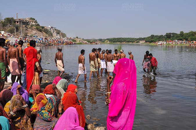 Fairs- Baneshwar Tribal Fair - Baneshwar, Dungarpur, Rajasthan, India- February 14, 2011: Devotees ready for the traditional ritual bath at the confluence of the rivers, Mahi and Som at Baneshwar, Dungarpur, Rajasthan, India by Anil