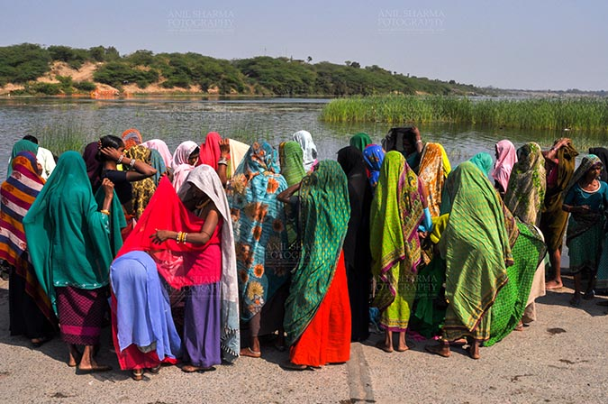 Fairs- Baneshwar Tribal Fair - Baneshwar, Dungarpur, Rajasthan, India- February 14, 2011: Bhil women in brightly coloured veils and saris covering their faces ready fot the ritual bath at Baneshwar Dungarpur, Rajasthan, India by Anil