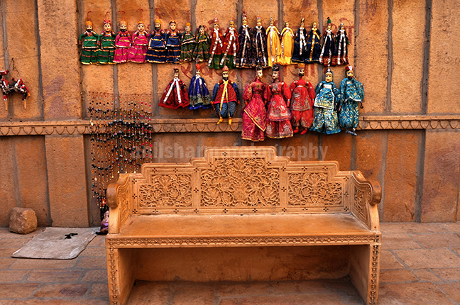Festivals- Jaisalmer Desert Festival, Rajasthan - Rajasthani Puppets hanging on the wall. by Anil