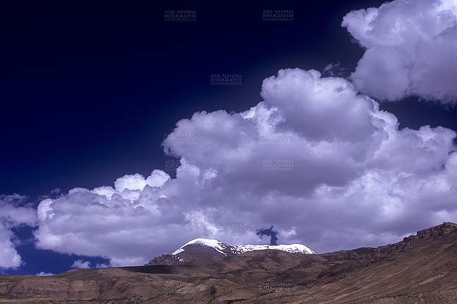 Clouds- Sky with Clouds (Kibber) - Sky with Clouds, Kibber, Spiti Valley, Himachal Pradesh, India- December 13, 2006: Dark blue sky with white clouds over the snow covered peaks at Kibber, Lahaul-Spiti, Himachal Pradesh, India. by Anil Sharma Fotography