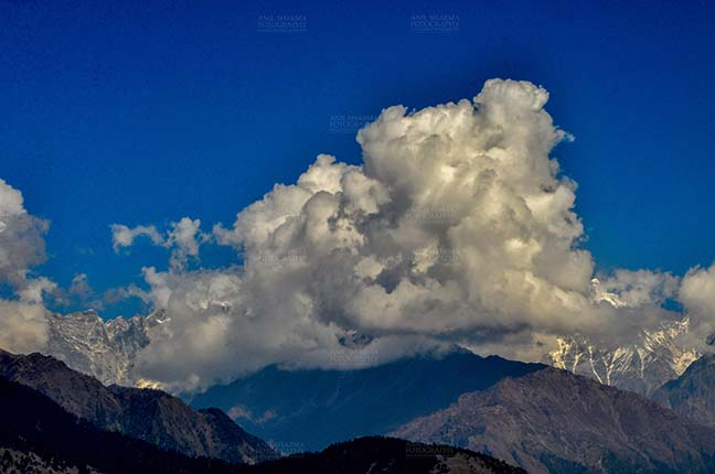 Clouds- Sky with Clouds (Panchchuli Peaks) - Panchchuli Peaks, Uttarakhand, India- November 2, 2016: Dark blue sky with bright white clouds covering the snow covered Punchchuli Peaks, view from Munsiyari, Uttarakhand, India. by Anil