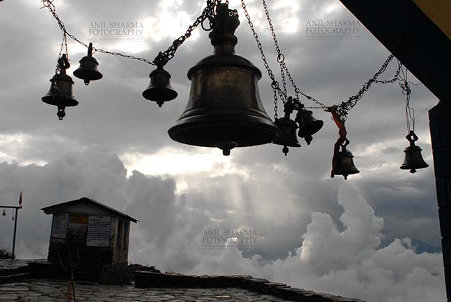 Religion- Tungnath Temple, Uttarakhand (India) - Tungnath, Chopta, Uttarakhand, India- August 18, 2009: Temple bells, Sun and Clouds at at Tungnath, Chpota, Uttarakhand, India. by Anil