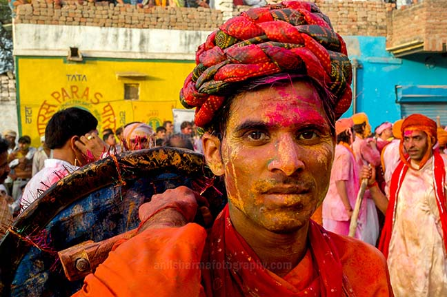 Festivals- Lathmaar Holi of Barsana (India) - A man daubed in color powder smiles as he celebrates lathmaar Holi at Barsana. by Anil