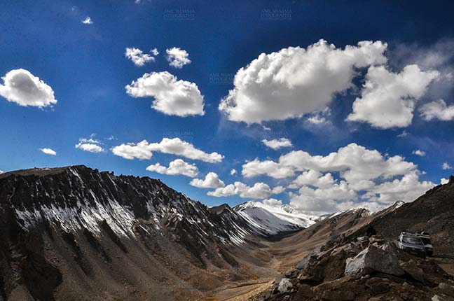 Clouds- Sky with Clouds (Khardung La) - Clouds over Khardung La, India- September 30, 2014 : Dark blue sky with white clouds floating over the snow covered mountain peaks at Khardung La, Leh, Jammu and Kashmir, India. by Anil Sharma Fotography
