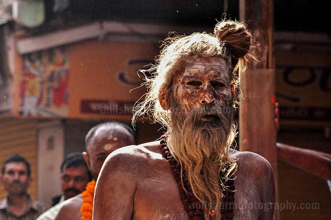 Culture- Naga Sadhu\u2019s (India) - An old Naga Sadhu wearing Rudraksha beads mala passing through a small lane of Varanasi. by Anil