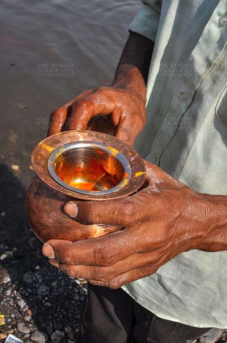Fairs- Baneshwar Tribal Fair - Baneshwar, Dungarpur, Rajasthan, India- February 14, 2011: A devotee holding saffron in a brass pot for the traditional ritual at the Baneshwar Mahadev at Baneshwar, Dungarpur, Rajasthan, India by Anil