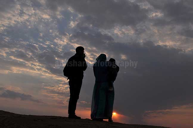 Festivals- Jaisalmer Desert Festival, Rajasthan - A family enjoying sunset scene at Jaisalmer desert fair. by Anil