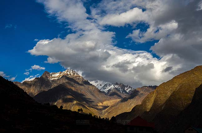 Clouds- Sky with Clouds (Jispa Village) - Clouds, Jispa, Himachal Pradesh, India- September 24, 2014: Dark blue sky with white clouds floating over the snow covered mountain peaks at Jispa Village, Lahaul-Spiti, Himachal Pradesh, India. by Anil