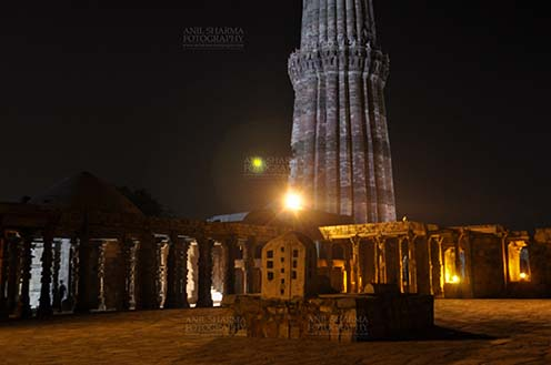 Monuments- Qutab Minar in Night, New Delhi, India. - The Beauty of arches of Iltutmish screen and some tourists standing near the iron pillar in night at Qutub Minar Complex, Mehrauli , New Delhi, India. by Anil