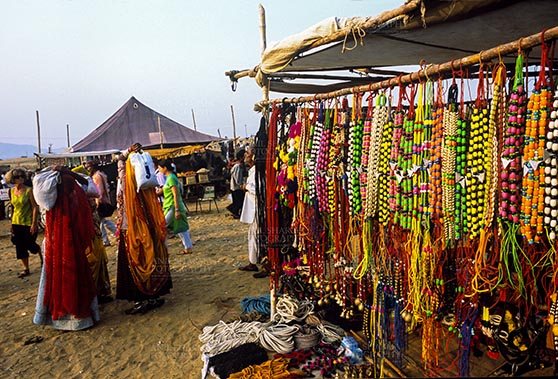 Fairs- Pushkar Fair (Rajasthan) - Pushkar, Rajasthan, India- May 23, 2008: Some tourists and a necklaces, beads, jewelry, gemstones, bracelets, earrings, bangles, and devotional object shop for religious ceremonies at Pushkar fair, Rajasthan, India. by Anil Sharma Fotography