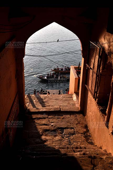 Travel- Varanasi the city of light (India) - View from an old building gates some pilgrims using boats to cross Holy River Ganges to reach their destination at Varanasi, Uttar Pradesh, India. by Anil