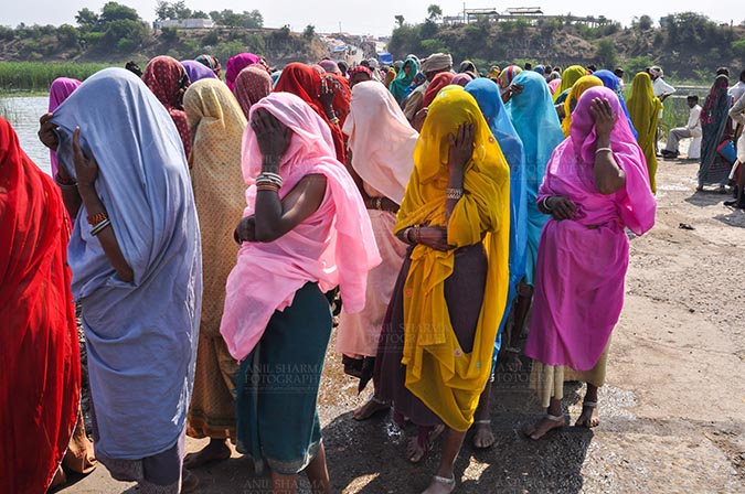 Fairs- Baneshwar Tribal Fair - Baneshwar, Dungarpur, Rajasthan, India- February 14, 2011: Bhil women in brightly coloured veils and saris covering their faces ready fot the ritual bath at Baneshwar Dungarpur, Rajasthan, India. by Anil Sharma Fotography