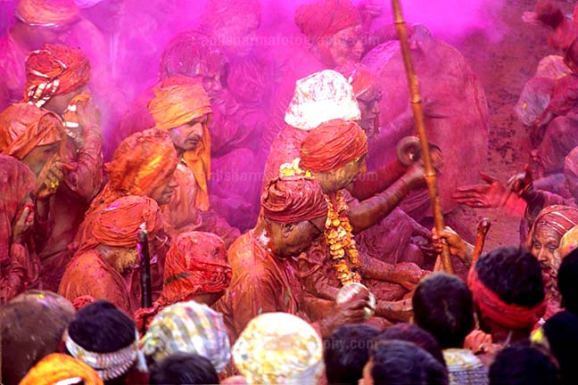 Festivals- Lathmaar Holi of Barsana (India) - People daubed in colored water, head covered singing a hymn during Lathmaar Holi celebrations at Barsana, Mathura, India. by Anil