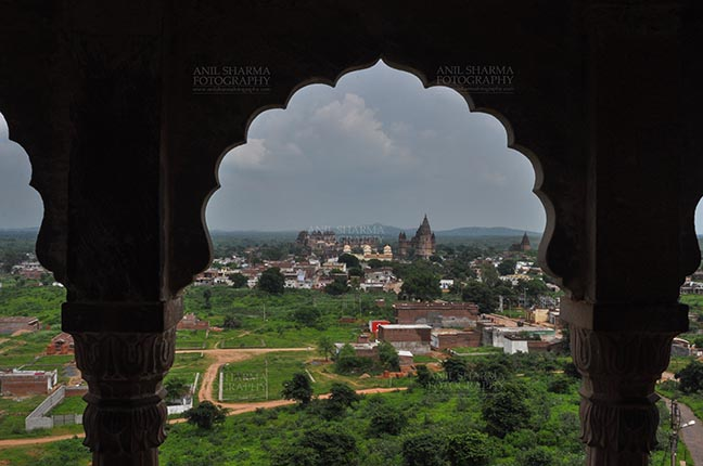 Monuments- Palaces and Temples of Orchha - Orchha, Madhya Pradesh, India- August 20, 2012: View from a carved window of Laxmi Temple, Chaturbhuj temple is seen in the distance, Orchha, Madhya Pradesh, India. by Anil