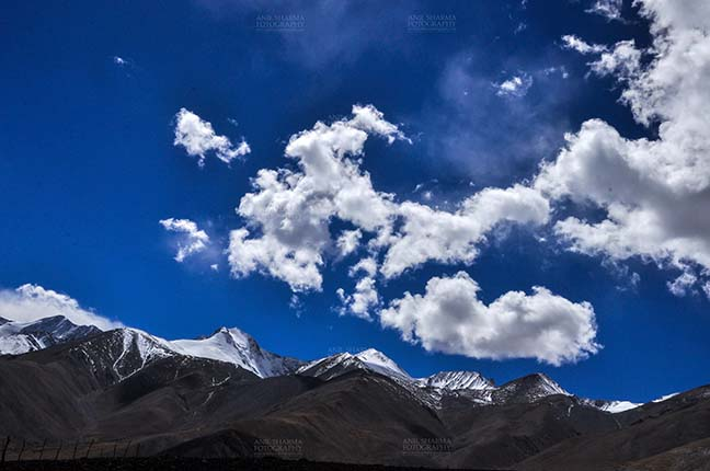 Clouds- Sky with Clouds (Pangong Tso) - Clouds over Pangong Tso, Leh, Jammu and Kashmir, India- October 1, 2014: Dark blue sky with Bright white clouds over the Pangong Tso and surrounding hills at Leh, Jammu and Kashmir, India. by Anil