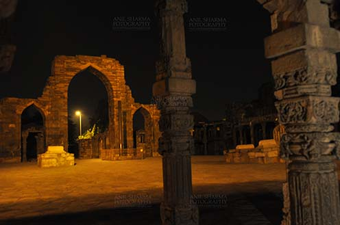 Monuments- Qutab Minar in Night, New Delhi, India. - Hindu Columns with stone carving at Quwwat-Ul-Islam mosque courtyard in night at Qutub Minar Complex, New Delhi, India. by Anil