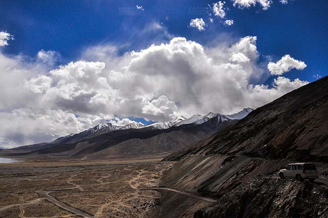 Clouds- Sky with Clouds (Pangong Tso, Leh) - Clouds over Pangong Tso, Leh, Jammu and Kashmir, India- October 1, 2014: Dark blue sky with Bright white clouds over the Pangong Tso and surrounding hills at Leh, Jammu and Kashmir, India. by Anil Sharma Fotography