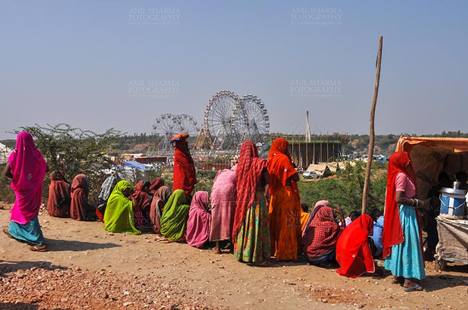 Fairs- Baneshwar Tribal Fair - Baneshwar, Dungarpur, Rajasthan, India- February 14, 2011: Bhil women in brightly coloured veils and saris enjoying panoramic view of the fair ground at Baneshwar Dungarpur, Rajasthan, India by Anil