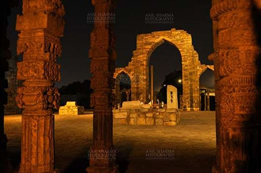 An ornately carved pillar and arches of Iltutmish screen at the Quwwat-Ul-Islam mosque in night at Qutub Minar Complex, Mehrauli , New Delhi, India.