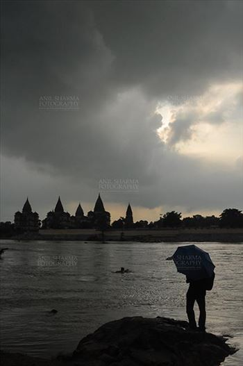 DSC_0337 Orchha, Madhya Pradesh, India- August 20, 2012: Chhatris on the bank of river Betwa, a tourist holding umbrella enjoying cloudy- rainy weather at Orchha, Madhya Pradesh, India.