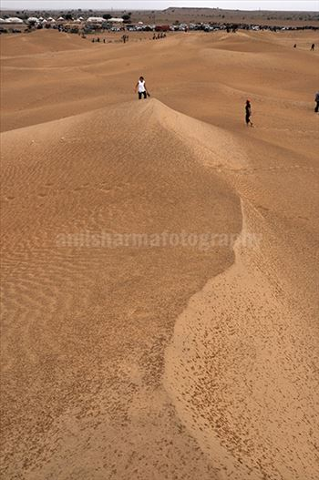 Festivals- Jaisalmer Desert Festival, Rajasthan - Tourists enjoy walking on the golden sand dunes in jaisalmer, Rajasthan.