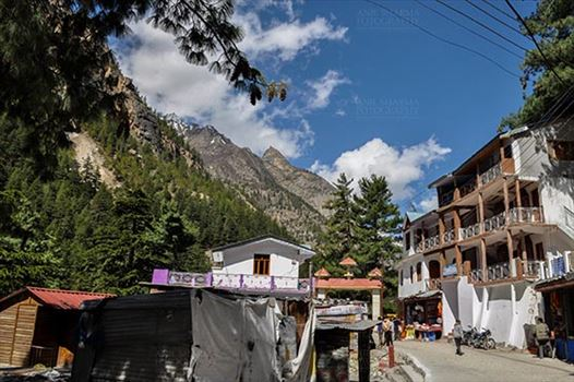 Gangotri, Uttarakhand, India- June 14, 2013: Hotel - houses on way to Gangotri temple with blue sky and snow covered mountain peaks at Gangotri, Uttarkashi, Uttarakhand, India.