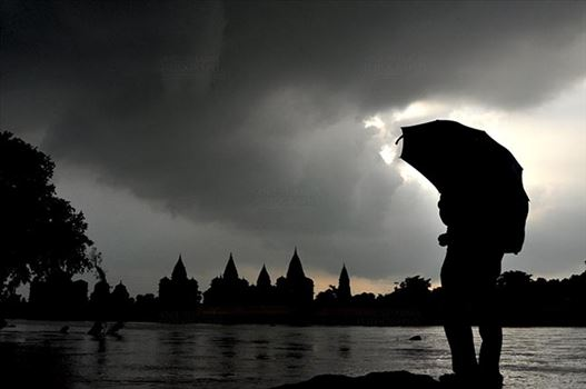 Orchha, Madhya Pradesh, India- August 20, 2012: Chhatris on the bank of river Betwa, a tourist holding umbrella enjoying cloudy- rainy weather at Orchha, Madhya Pradesh, India.