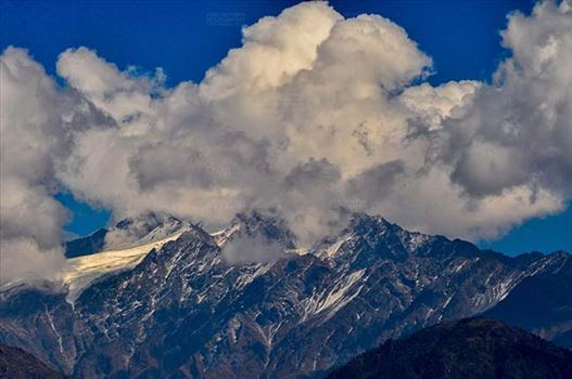 Clouds- Sky with Clouds (Panchchuli Peaks) - Panchchuli Peaks, Munsiyari, Uttarakhand, India- November 2, 2016: Blue sky with bright white clouds over the snow covered Punchchuli Peaks view from Munsiyari, Uttarakhand, India.