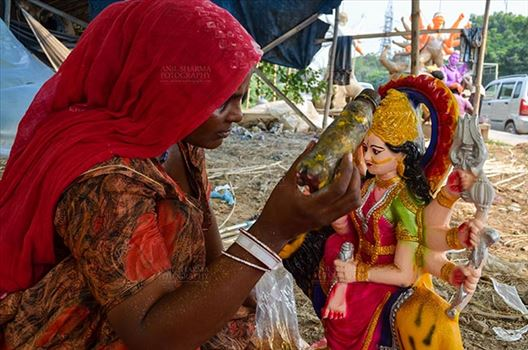 Durga Puja Festival, Noida, Uttar Pradesh, India- September 20, 2017: A Rajasthan tribal artist giving final touches to the Goddess Durga's clay idol at Noida, Uttar Pradesh, India.