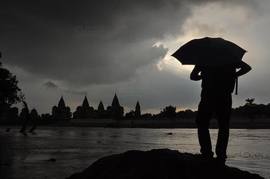 Orchha, Madhya Pradesh, India- August 20, 2012: Chhatris on the bank of river Betwa, a tourist holding umbrella enjoying cloudy- rainy season at Orchha, Madhya Pradesh, India.
