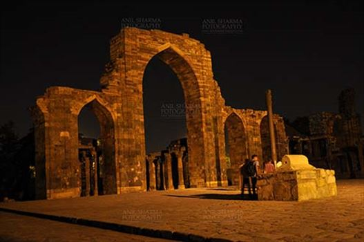 The Beauty of arches of  Iltutmish screen and some tourists standing near the  iron pillar in night at Qutub Minar Complex, Mehrauli , New Delhi, India.
