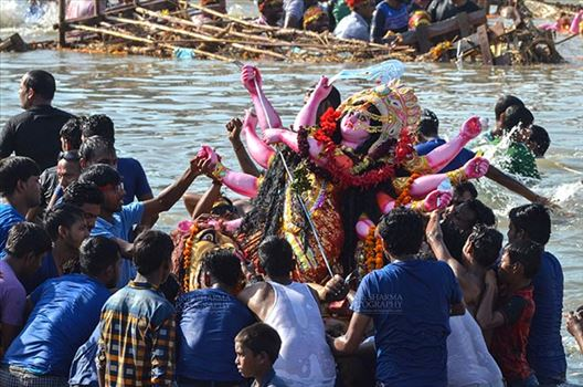 Durga Puja Festival, New Delhi, India-September 30, 2017: Hindu devotees immersing idol of Goddess Durga in river Yamuna at Kalindi Kunj, New Delhi, India.
