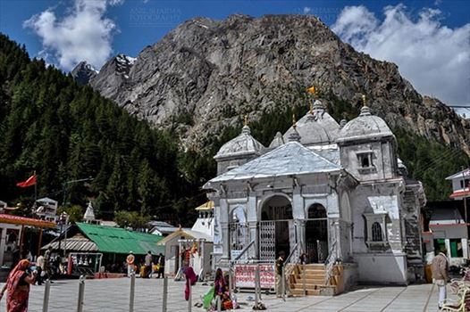 Gangotri, Uttarakhand, India- May 13, 2015: Snow peaks, blue sky and Devotees at Goddess Ganges Temple, Gangotri, Uttarkashi, Uttarakhand, India.