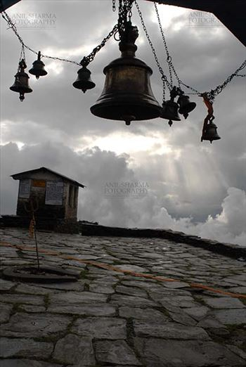 Tungnath, Chopta, Uttarakhand, India- August 18, 2009: Sun piercing the cloudes and temple bells at Tungnath Temple, Chpota, Uttarakhand, India.