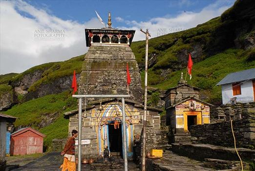 Tungnath, Chopta, Uttarakhand, India- August 18, 2009: Hanging bells, red color flags and temple prist at Tungnath temple complex at Tungnath, Chpota, Uttarakhand, India.