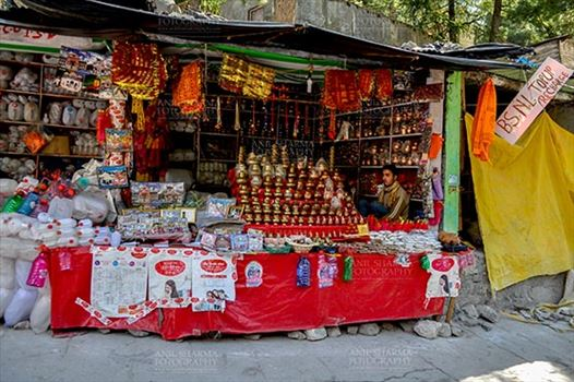 Gangotri, Uttarakhand, India- May 13, 2015: A shopkeepers selling plastic bottles and devotional objects, for religious ceremonies at Gangotri, Uttarkashi, Uttarakhand, India.