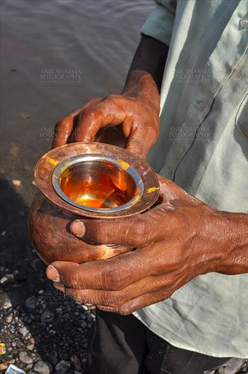 Baneshwar, Dungarpur, Rajasthan, India- February 14, 2011: A devotee holding saffron in a brass pot for the traditional ritual at the Baneshwar Mahadev at Baneshwar, Dungarpur, Rajasthan, India