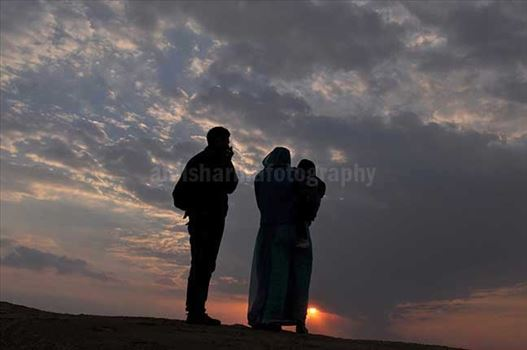 Festivals- Jaisalmer Desert Festival, Rajasthan - A family enjoying sunset scene at Jaisalmer desert fair.