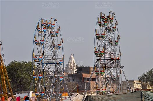 Baneshwar, Dungarpur, Rajasthan, India- February 14, 2011: View of Baneshwar Mahadev temple standing between two ferris wheels at Baneshwar, Dungarpur, Rajasthan, India.