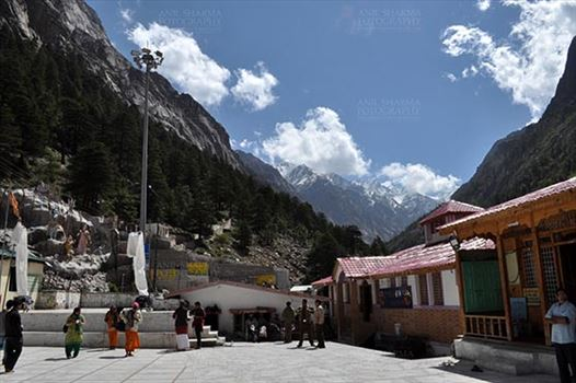 Gangotri, Uttarakhand, India- May 13, 2015: Hindu Devotees at Goddess Ganges Temple and snow covered Himalalyan peaks all around at Bhagirathi valley at Gangotri, Uttarkashi, Uttarakhand, India.