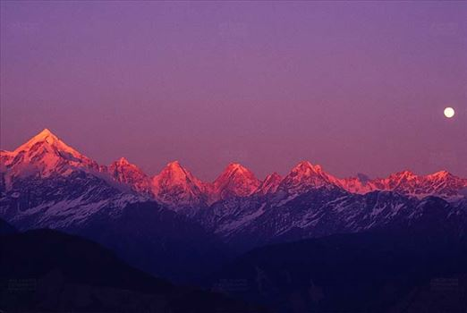 Mountains- Panchchuli Peaks (India) - Pink color Panchchuli Peaks and full moon in the sky view from Munsyari at Uttarakhand, India.