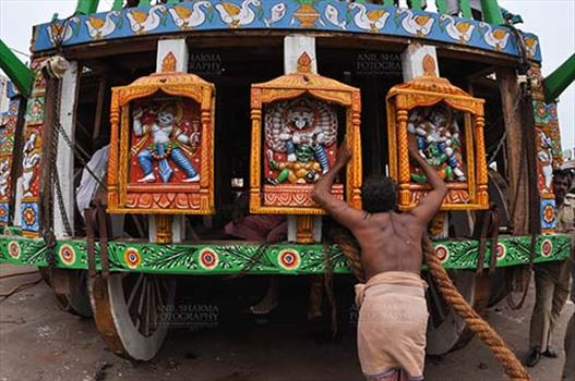 A devotee praying to the idols assembled on the chariot for Jagannath Rath Yatra festival at Puri, Odisha, India.