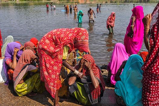 Baneshwar, Dungarpur, Rajasthan, India- February 14, 2011: Bhil women in brightly coloured veils and saris covering their faces ready for the ritual bath at Baneshwar Dungarpur, Rajasthan, India