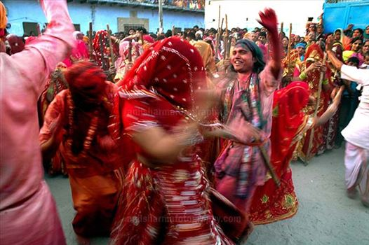 "Some women dancing some holding bamboo sticks, during "" Lathmaar Holi"" at Mathura, Uttar Pradesh, India."
