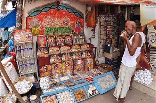 Festivals- Jagannath Rath Yatra (Odisha) - Memento of Lord Jagannath, Balbhadra and Subhadra on display and an old customer at the shop near Lord Jagannath Temple at Puri, Odisha, India.